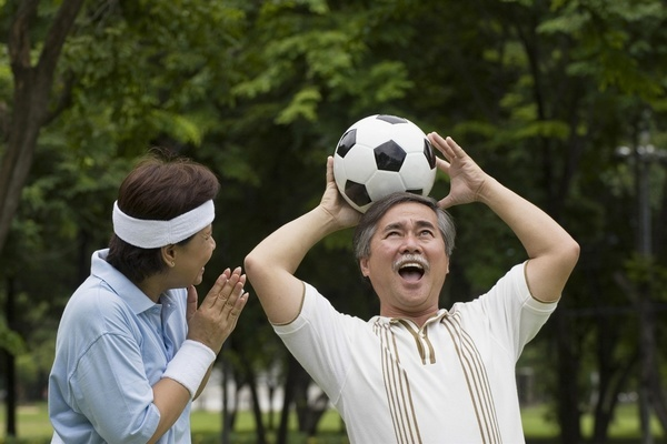 An Asian man playing around with a soccer ball.  MODEL RELEASED