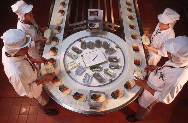 Working on a conveyor belt, Thai chefs help package up some pre-prepared meals that are ready to put on Emirates airlines aircraft. The meals have been prepared in Bangkok by Gate Gourmet, an international airline catering company. The cuisine on Emirates Airlines has been praised for its quality.