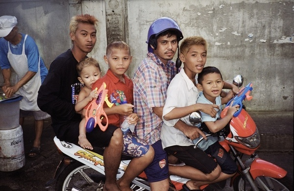 A family of six aboard a motorcycle during the traditional Sonkran festivities in downtown Bangkok.  Each year, in the second week of April, Thais young and old dowse each other with water echoing an ancient ritual marking the advent of the Thai Lunar New Year. Although rooted in a restrained gesture whereby water was poured onto the nape, the festival has evolved into one of the planet's largest annual water battles.