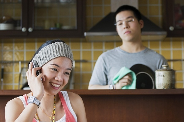Young Asian woman talking on the phone with husband looking on.  MODEL RELEASED
