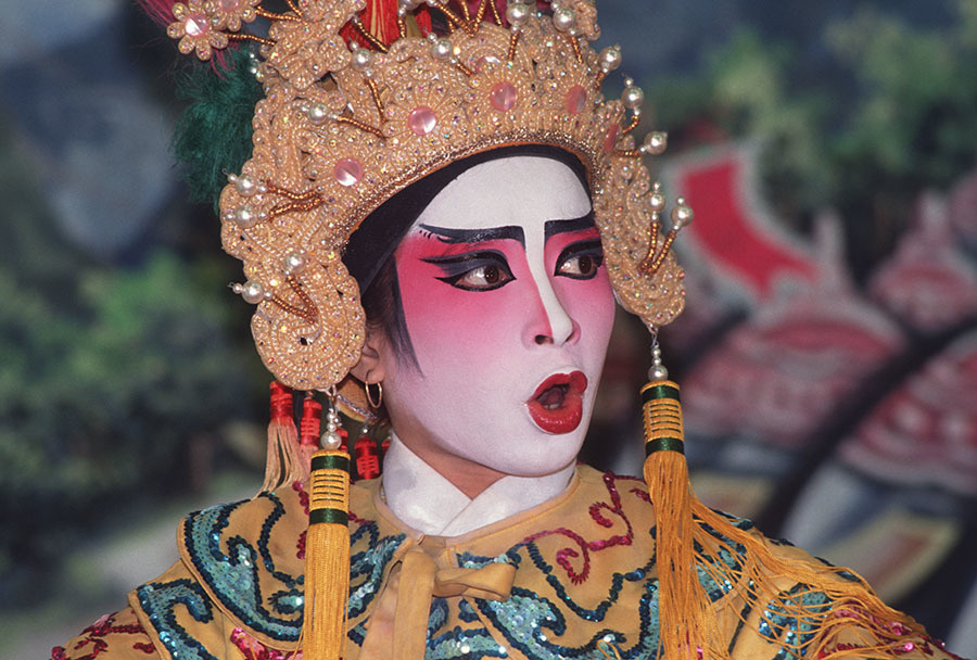 The heavily made up face of  a character singing in a Chinese opera performance known as 'Ngiew' in Thailand.