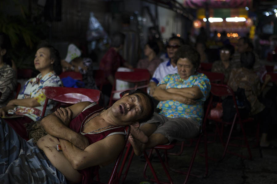 The audience looks less than enthralled during a Chinese Opera performance in Bangkok. Chinese opera is performed in Thailand by itinerant groups of players, most of whom are from the northeastern region of Thailand known as Isan. It is characterised by its lavish costumes, the falsetto delivery of its actors and the highly stylised presentation of its set-piece stories which are drawn from Chinese folklore. Though the operas are performed in Chinese most of the actors don't understand Chinese and simply learn their parts by rote. Chinese opera is colourful reminder of the importance of Thailand's ethnic Chinese population, and of how Chinese culture has become an integral part of Thailand's cultural identity. Though the Chinese opera is appreciated by an ageing, and dwindling, population of Chinese speakers, the performers explain that audience sizes is of little importance since they essentially performing for the gods. The shows are usually sponsored by the local community, are free for all to attend and usually last between two and three days.
