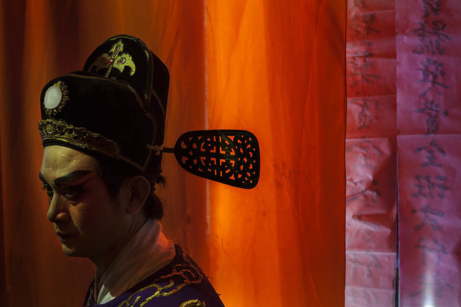 A back stage scene during a Chinese opera performance in Bangkok. Chinese opera is performed in Thailand by itinerant groups of players, most of whom are from the northeastern region of Thailand known as Isan. It is characterised by its lavish costumes, the falsetto delivery of its actors and the highly stylised presentation of its set-piece stories which are drawn from Chinese folklore. Though the operas are performed in Chinese most of the actors don't understand Chinese and simply learn their parts by rote. Chinese opera is colourful reminder of the importance of Thailand's ethnic Chinese population, and of how Chinese culture has become an integral part of Thailand's cultural identity. Though the Chinese opera is appreciated by an ageing, and dwindling, population of Chinese speakers, the performers explain that audience sizes is of little importance since they essentially performing for the gods. The shows are usually sponsored by the local community, are free for all to attend and usually last between two and three days.