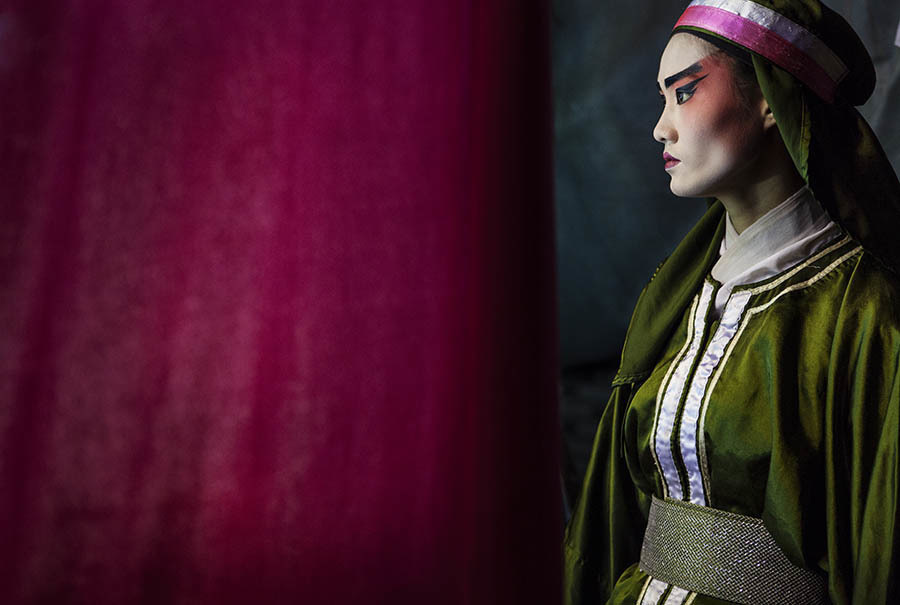 A Chinese Opera performer waits to go on stage during a show in Bangkok. Chinese opera is performed in Thailand by itinerant groups of players, most of whom are from the northeastern region of Thailand known as Isan. It is characterised by its lavish costumes, the falsetto delivery of its actors and the highly stylised presentation of its set-piece stories which are drawn from Chinese folklore. Though the operas are performed in Chinese most of the actors don't understand Chinese and simply learn their parts by rote. Chinese opera is colourful reminder of the importance of Thailand's ethnic Chinese population, and of how Chinese culture has become an integral part of Thailand's cultural identity. Though the Chinese opera is appreciated by an ageing, and dwindling, population of Chinese speakers, the performers explain that audience sizes is of little importance since they essentially performing for the gods. The shows are usually sponsored by the local community, are free for all to attend and usually last between two and three days.