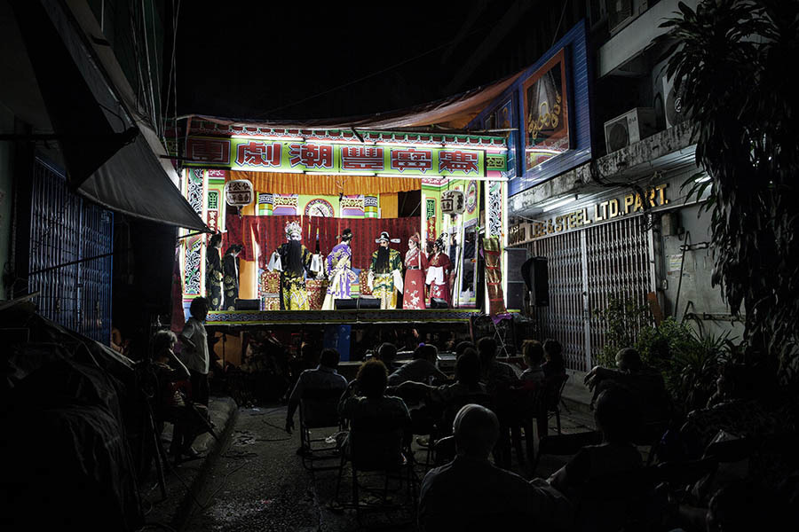 A view of a Chinese Opera stage set up in a small side street in Bangkok's Chinatown district. Chinese opera is performed in Thailand by itinerant groups of players, most of whom are from the northeastern region of Thailand known as Isan. It is characterised by its lavish costumes, the falsetto delivery of its actors and the highly stylised presentation of its set-piece stories which are drawn from Chinese folklore. Though the operas are performed in Chinese most of the actors don't understand Chinese and simply learn their parts by rote. Chinese opera is colourful reminder of the importance of Thailand's ethnic Chinese population, and of how Chinese culture has become an integral part of Thailand's cultural identity. Though the Chinese opera is appreciated by an ageing, and dwindling, population of Chinese speakers, the performers explain that audience sizes is of little importance since they essentially performing for the gods. The shows are usually sponsored by the local community, are free for all to attend and usually last between two and three days.