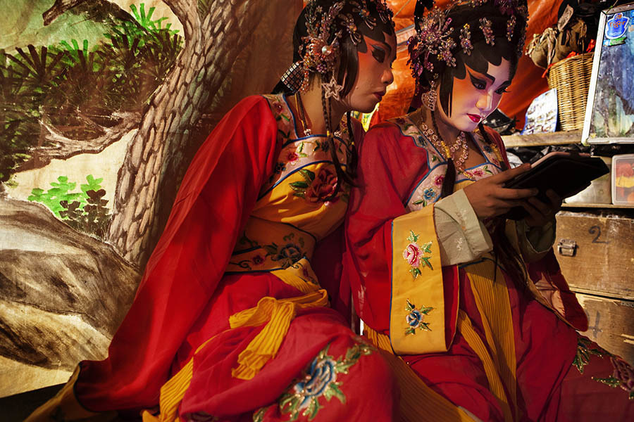 Two Chinese Opera performers play on a tablet computer between acts. Chinese opera is performed in Thailand by itinerant groups of players, most of whom are from the northeastern region of Thailand known as Isan. It is characterised by its lavish costumes, the falsetto delivery of its actors and the highly stylised presentation of its set-piece stories which are drawn from Chinese folklore. Though the operas are performed in Chinese most of the actors don't understand Chinese and simply learn their parts by rote. Chinese opera is colourful reminder of the importance of Thailand's ethnic Chinese population, and of how Chinese culture has become an integral part of Thailand's cultural identity. Though the Chinese opera is appreciated by an ageing, and dwindling, population of Chinese speakers, the performers explain that audience sizes is of little importance since they essentially performing for the gods. The shows are usually sponsored by the local community, are free for all to attend and usually last between two and three days.