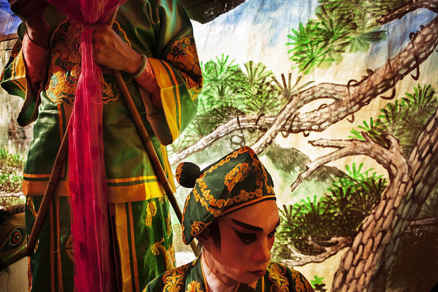 A performer relaxes behind the scenes during a Chinese Opera performance in Bangkok. Chinese opera is performed in Thailand by itinerant groups of players, most of whom are from the northeastern region of Thailand known as Isan. It is characterised by its lavish costumes, the falsetto delivery of its actors and the highly stylised presentation of its set-piece stories which are drawn from Chinese folklore. Though the operas are performed in Chinese most of the actors don't understand Chinese and simply learn their parts by rote. Chinese opera is colourful reminder of the importance of Thailand's ethnic Chinese population, and of how Chinese culture has become an integral part of Thailand's cultural identity. Though the Chinese opera is appreciated by an ageing, and dwindling, population of Chinese speakers, the performers explain that audience sizes is of little importance since they essentially performing for the gods. The shows are usually sponsored by the local community, are free for all to attend and usually last between two and three days.