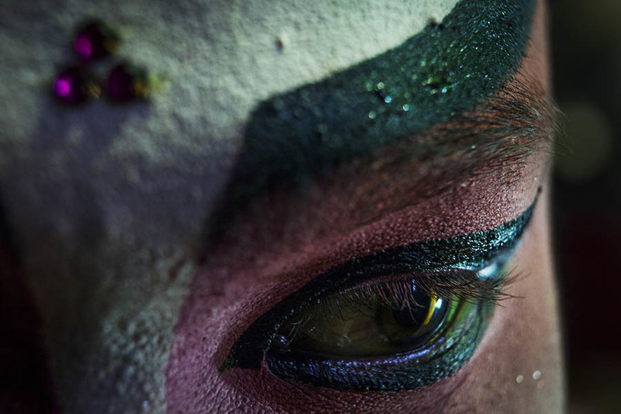A close up of the make up around a Chinese opera performer's eye. Chinese opera is performed in Thailand by itinerant groups of players, most of whom are from the northeastern region of Thailand known as Isan. It is characterised by its lavish costumes, the falsetto delivery of its actors and the highly stylised presentation of its set-piece stories which are drawn from Chinese folklore. Though the operas are performed in Chinese most of the actors don't understand Chinese and simply learn their parts by rote. Chinese opera is colourful reminder of the importance of Thailand's ethnic Chinese population, and of how Chinese culture has become an integral part of Thailand's cultural identity. Though the Chinese opera is appreciated by an ageing, and dwindling, population of Chinese speakers, the performers explain that audience sizes is of little importance since they essentially performing for the gods. The shows are usually sponsored by the local community, are free for all to attend and usually last between two and three days.