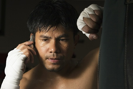 A boxer takes a break to talk on his mobile phone during a training session at the gym.  MODEL RELEASED