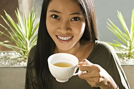 Young Asian woman enjoying a cup of tea.  MODEL RELEASED